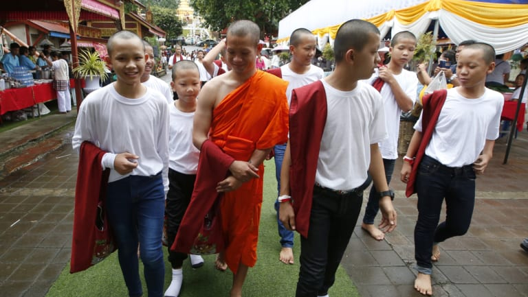 Members of Wild Boars soccer team walk with Buddhist monk, former soccer coach Ekkapol Chanthawong, in red, after the completion of their serving as novice Buddhist monks.