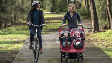 Labor spokeswoman for active transport Jo Haylen, with her children Dylan and Elliot, chats to cyclist Felicity Wade in Beaman Park, Earlwood.