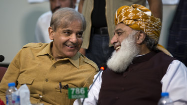 Maulana Fazlur Rehman, right, head of Pakistani religious parties alliance talks to Shahbaz Sharif, leader of Pakistan Muslim League and brother of ousted prime minister Nawaz Sharif during an All Parties Conference in Islamabad, Pakistan, on Friday.
