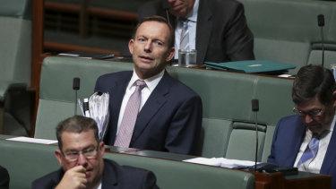 Tony Abbott watches on.