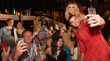Guy Sebastian and Delta Goodrem pose for selfies with fans on the red carpet.
