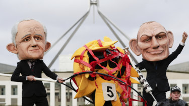 Puppets of Malcolm Turnbull and Tony Abbott rig the sun versus coal race in a protest outside Parliament