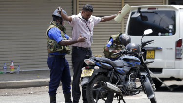Navy soldiers perform security checks on motorists at a roadside in Colombo.