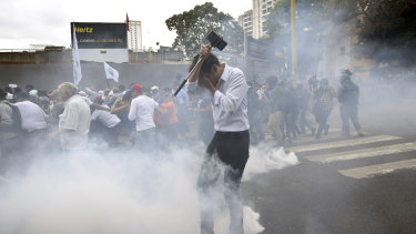 People were hit with tear gas during an opposition march in Caracas on Tuesday.