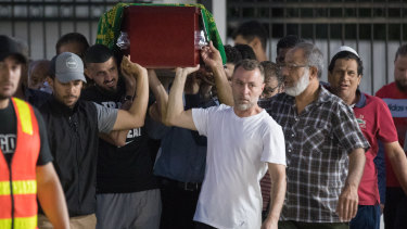 Pallbearers carry Aiia's coffin.