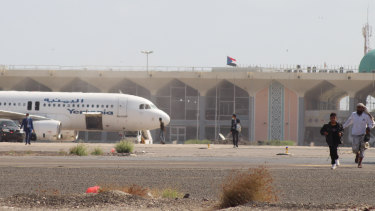 People walk away from the runway following an explosion at the airport in Aden, Yemen.
