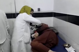 A medical worker attends to someone wounded in the deadly Kabul airport attack.