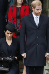 Prince Harry, stands with Meghan, Duchess of Sussex as she does a curtsy to the Queen after the Christmas day service.