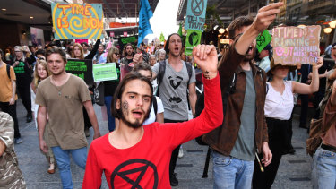 Eric Herbert (centre) with the Extinction Rebellion protesters as they march down the Queen Street Mall.