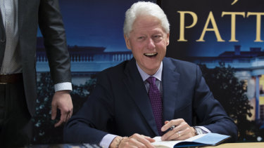 Former US president Bill Clinton smiles as he signs autographs during an event to promote his new novel with author James Patterson, The President is Missing.