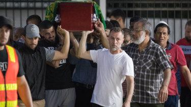 Pallbearers carry Aiia's coffin.