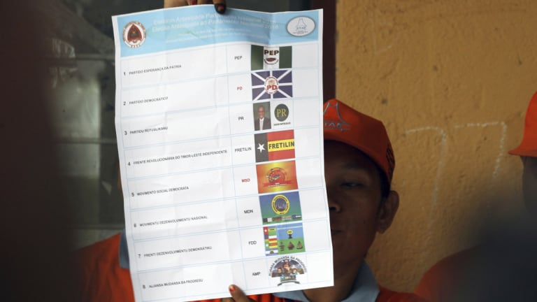 An electoral worker inspects a ballot at a polling station during the vote counting following the parliamentary election in Dili, East Timor, on Saturday.