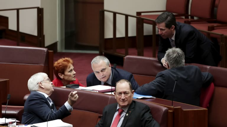 Education Minister Simon Birmingham, right, talks with members of the crossbench.
