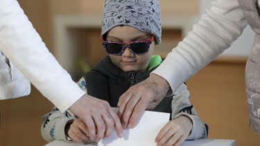 A child assists his relatives their votes at a polling station during the second round of the presidential election in Bratislava, Slovakia, on Saturday, March 30.