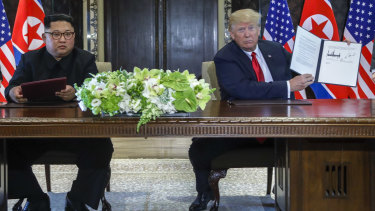 US President Donald Trump holds up the document that he and North Korean leader Kim Jong-un signed in Singapore agreeing to the repatriation of the remains of US military personnel missing in action from the Korean War.