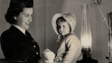When a take-off from Sydney Airport (Mascot) was delayed by a sudden fuel strike, the interior of this Qantas Constellation was lit with kerosene lamps while the dispute was resolved. In the galley, hostess Patricia Burke comforted a young passenger.