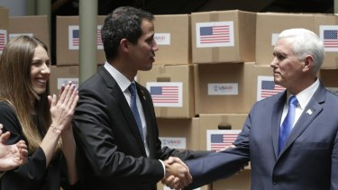 Venezuela's self-proclaimed interim president Juan Guaido, centre, shakes hands with US Vice-President Mike Pence in a room filled with humanitarian aid in Bogota, Colombia. Guaido's wife Fabiana Rosales is pictured left.