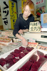 Salesperson Yoko Yoshimura arranges cuts of raw whale meat at her shop at a port in Shimonoseki, Japan.