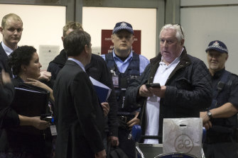 Music promoter Andrew McManus, wearing a white shirt, was detained at Melbourne Airport in 2015. He pleaded guilty to lying to police over a $702,000 bag of cash.