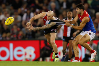 St Kilda's Zak Jones is tackled by Melbourne's Christian Petracca.