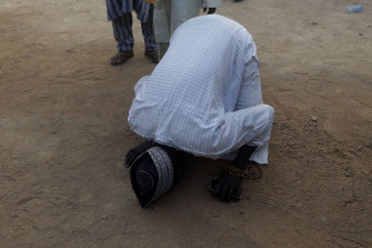 A father kisses the ground to give thanks for the safe return of his kidnapped son, Katsina, Nigeria.