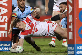 Cameron McInnes crashes through two Sharks defenders to score on Sunday.
