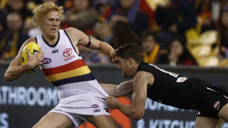 Elliott Himmelberg is tackled by Carlton's Sam Rowe.