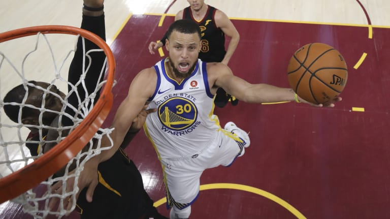 Stephen Curry goes to the basket.