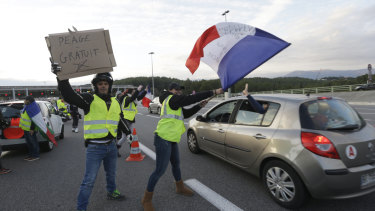 "Protesters wearing yellow vests wave a French flag and a poster reading ""Free toll"" as they open the toll gates on a motorway in Antibes, southern France, on Monday."