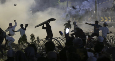 Hundreds of protesters have been taken into custody and accused of receiving cash rewards for rioting in Jakarta.