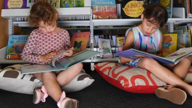 The Leong sisters - Olivia, 4, and Isabelle, 7 - read books in the tiny children's section of the State Library of NSW. Planning for a new dedicated children's library is under way.