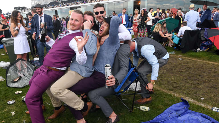Race fans enjoy the last moments of a muddy Melbourne Cup day.