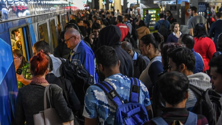 Commuters pour onto a train at Southern Cross Station on Thursday.
