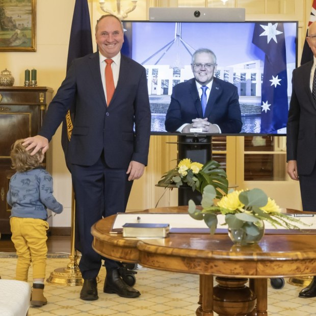 Re-elected Nationals leader Barnaby Joyce poses for a picture during the  swearing-in ceremony as Deputy Prime Minister, as his son Sebastian runs up to him.