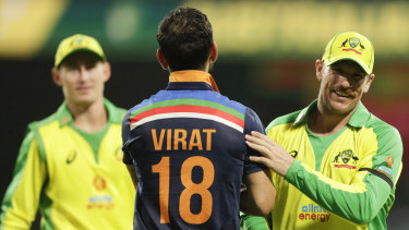 Virat Kohli congratulates Aaron Finch after Australia's victory.