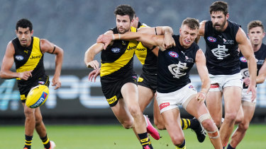 Back in the beginning: Carlton captain Patrick Cripps heads for the loose ball against Richmond's Trent Cotchin during the opening match of season 2020 at the MCG.