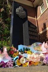 Flowers are left as a memorial for slain officer Senior Constable Brett Forte at Toowoomba police station.