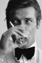 Roger Moore, well known for his roles as James Bond, downs a martini.