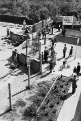 Residents of West Berlin [R], watch East German construction workers erect the wall.