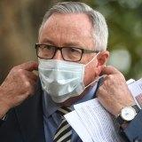 Health Minister Brad Hazzard dons a mask at Tuesday's coronavirus briefing.