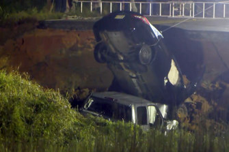 A vehicle is salvaged from a hole left on highway 26 near Lucedale, Mississippi on Tuesday.