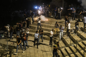 Palestinians escape from a stun grenade fired by Israeli police officers during clashes at Damascus Gate during Ramadan in Israeli-occupied East Jerusalem on May 8, 2021.