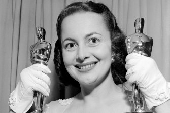 Olivia de Havilland holds two Oscars as she returns home following the Academy Awards presentation in 1950.