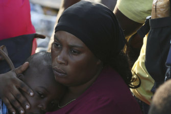 A woman on Abaco Island comforts her child.