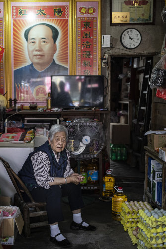 A woman sits in her shop, a poster of Mao hanging behind her, in Hong'an county in June 2021.