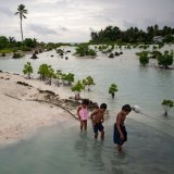 Children wade through water at high tide in the village of Abarao on the Pacific nation of Kiribati, one of the countries most vulnerable to climate change.