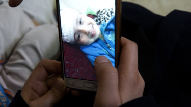 Aisha al-Lulu's mother Muna Awad shows a photo of the five-year-old in a Jerusalem hospital.