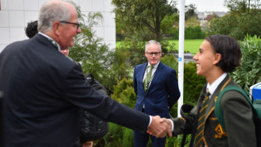 Trinity Grammar head master Dr Michael Davies (centre) looks on as Mr Brown (left) greets students.