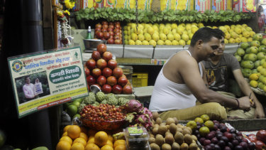 A Mumbai fruit vendor displays a placard informing shoppers about the use of non-plastic bags.