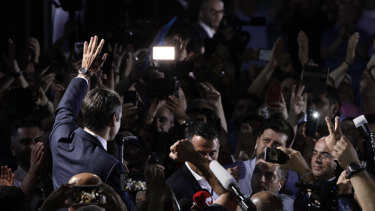 Mitsotakis waves to supporters outside party headquarters.